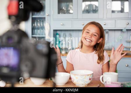 Pre-teen girl video blogging in the kitchen waving her hands - Stock Photo