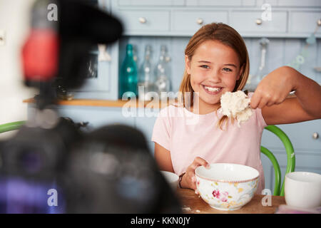 Young girl video blogging in kitchen showing spoon of dough - Stock Photo