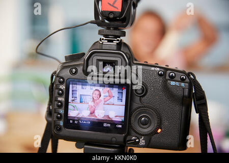 Girl video blogging in kitchen seen through camera, close up - Stock Photo