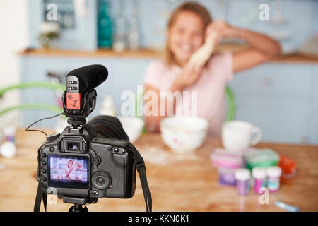 Young girl video blogging in kitchen seen through camera - Stock Photo