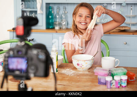 Young girl video blogging in a kitchen showing dough mixture - Stock Photo
