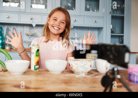 Girl video blogging in the kitchen smiling and showing hands - Stock Photo