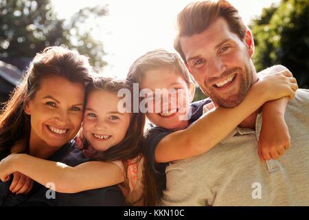 Portrait Of Parents Giving Children Piggyback In Garden - Stock Photo