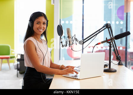 Young mixed race woman recording a podcast smiling to camera - Stock Photo