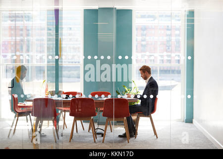 Young businessman working alone in an office meeting room - Stock Photo
