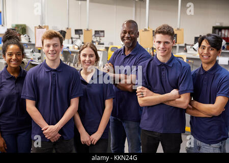Portrait Of Engineer And Apprentices In Factory - Stock Photo
