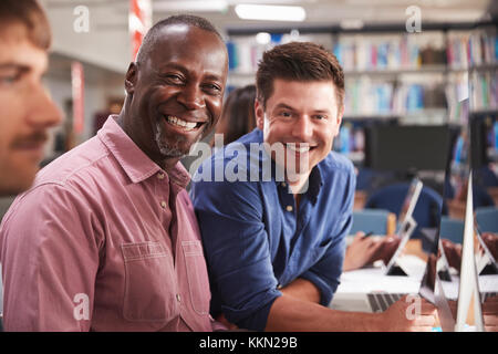 Mature Male Student With Tutor Learning Computer Skills - Stock Photo