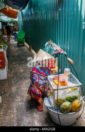 Local lifestyle: woman with food for sale in panniers, Binh Tay OR Hoa Binh Market, Chinatown (Cholon), Saigon (Ho - Stock Photo