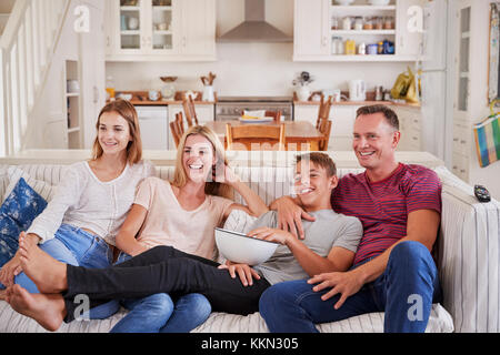 Family With Teenage Children Sitting On Sofa Watching TV Together - Stock Photo