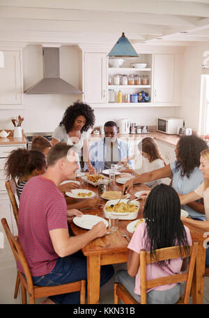Two Families Enjoying Eating Meal At Home Together - Stock Photo