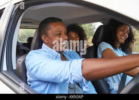 Family With Teenage Children In Car On Road Trip - Stock Photo
