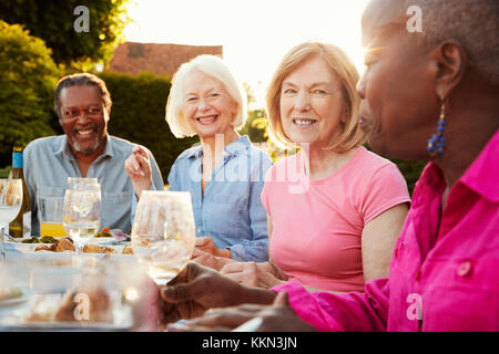 Group Of Senior Friends Enjoying Outdoor Dinner Party At Home - Stock Photo