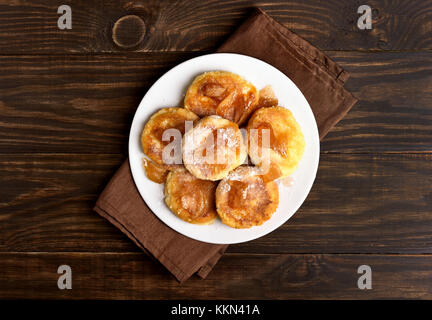 Fritters, curd cheese pancakes with caramelized apple slices on wooden table. Top view, flat lay - Stock Photo