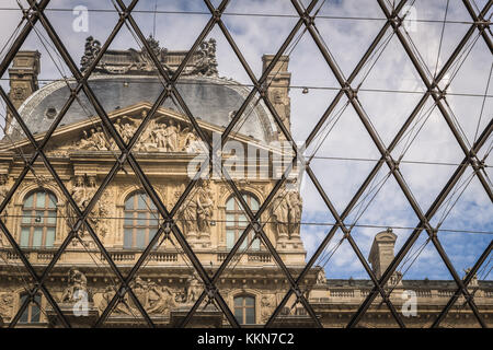 View of the Louvre from inside the glass pyramid. Louvre Museum is one of the largest and most visited museums worldwide, - Stock Photo