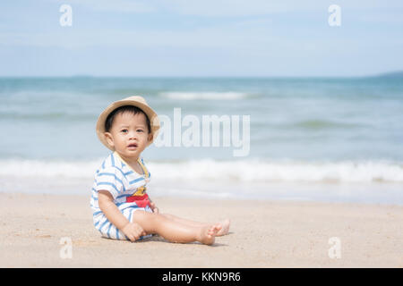 Portrait of a 10 months Asian baby boy with a hat sit in beach near sea in Phuket, Thailand. Summer, vacation, Travel - Stock Photo