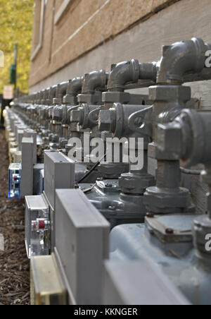 Row gray gas meters on the side of a building, perspective falling away - Stock Photo