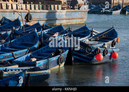Small blue fishing boats jumbled together in port - Stock Photo