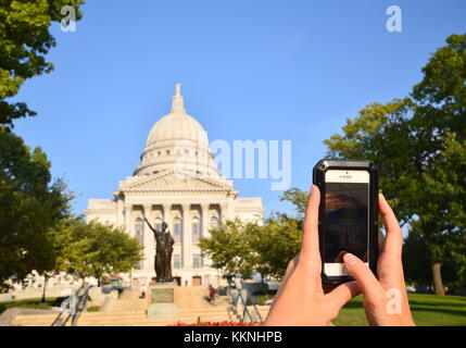 MADISON, WISCONSIN - SEPTEMBER 12, 2017 : Personal Perspective pov of woman taking photograph with a smartphone - Stock Photo