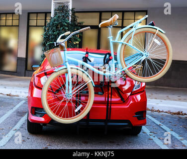 Blue bicycle with basket fastened to back of red sports car parked in front of shops - Stock Photo