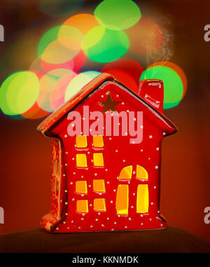 Beautiful Christmas decorations, cute little red decorative house over blurry lights background, festive Christmastime - Stock Photo