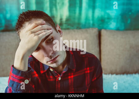 side profile stressed sad young crying man sitting outside holding head with hands looking down. Human emotion feelings. - Stock Photo