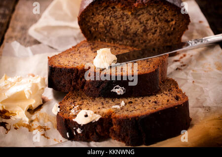 Slices of dark bread and milk butter.Selective focus on the butter on knife - Stock Photo