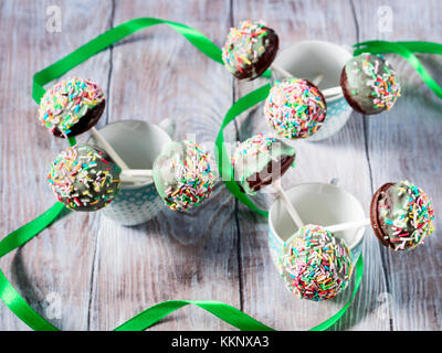 Closeup of colorful chocolate cake pops with sugar sprinkles in small coffee cups on wooden table. Children party - Stock Photo