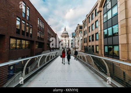 People walking on Millennium Bridge towards St Paul's Cathedral in winter London - Stock Photo