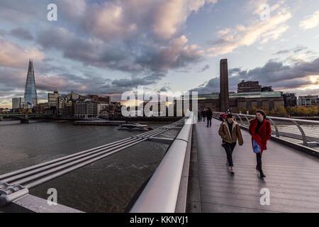 People walking on Millennium Bridge on winter London skyline - Stock Photo