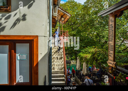 A woman and a black and white cat on a staircase near an outdoor cafe along the river Neretva near the old Bridge - Stock Photo