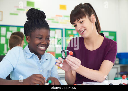 Female Pupil And Teacher Using Molecular Model Kit In Science Lesson - Stock Photo