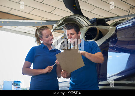 Aero Engineer And Apprentice Working On Helicopter In Hangar Looking At Clipboard - Stock Photo