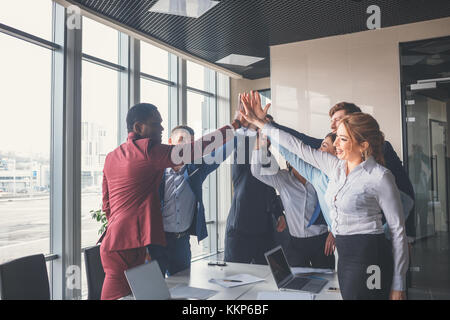 business team giving a high fives gesture as they laugh and cheer their success - Stock Photo