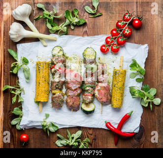 Tasty Meat Skewers  for grill with vegetables , corn ears and condiment on rustic background , top view - Stock Photo