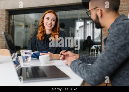 Smiling woman being interviewed by headhunter - Stock Photo
