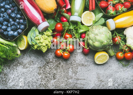 Various colorful smoothie and juices in bottles with fresh organic vegetables and fruits on grey concrete background, - Stock Photo