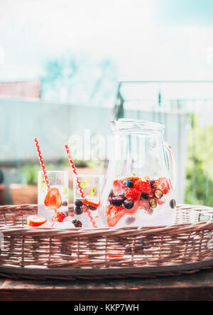 Berries Infused water with ice cubes in jug on tray at outdoor nature background, front view - Stock Photo