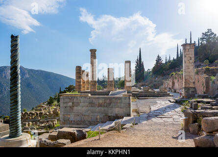 Temple of Apollo with a replica of the Serpent Column in the left foreground, Delphi, Greece - Stock Photo