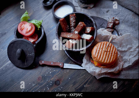 Burger with garlic croutons in the dark interior of the pub. Hearty, quick lunch.Atmospheric photo - Stock Photo
