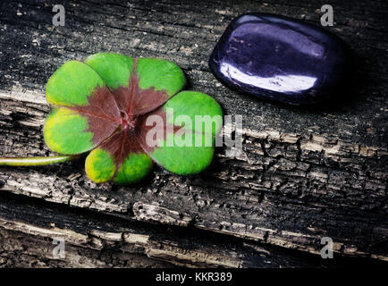 Four-leafed clover, cloverleaf and stone on wood - Stock Photo