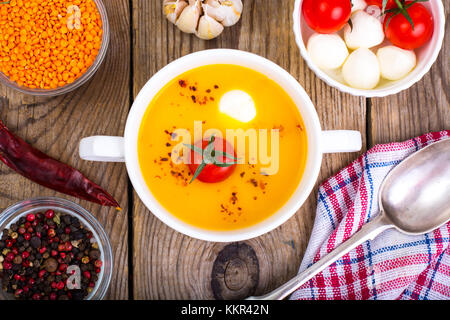 White bowl with cream soup of lentils, tomatoes and mozzarella - Stock Photo