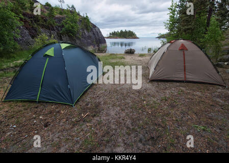 Tourist camp with two tents and inflatable boat at the river or lake bank. Camp is located among the forest and - Stock Photo