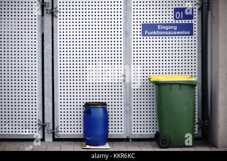 Waste containers standing in front of a (paled) gate made of perforated metal plate. - Stock Photo
