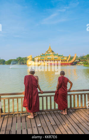Yangon, Myanmar (Burma). Two monks watching the Karaweik Palace on the Kandawgyi Lake. - Stock Photo