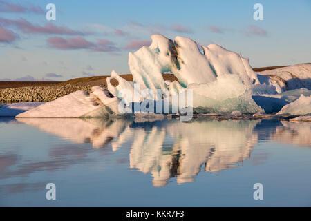 Iceberg reflection in Jokulsarlon Glacier Lagoon during a sunrise, Austurland, Eastern Iceland, Iceland - Stock Photo