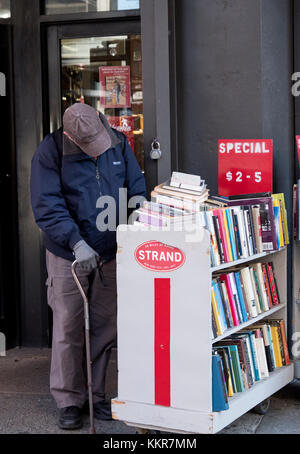 An unidentified senior citizen with a cane browsing the sale book racks outside the Strand bookstore on Broadway - Stock Photo