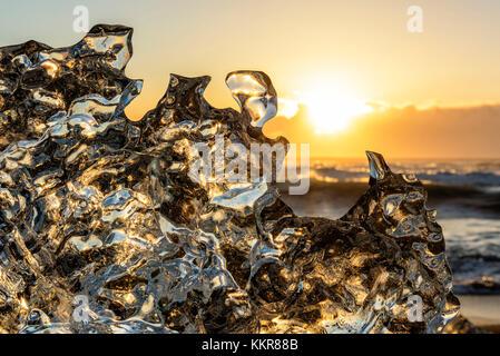 Jokulsarlon glacier lagoon, Iceland. Sunlight reflections over a small black of ice on the shore. - Stock Photo