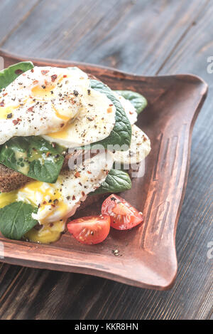 Sandwich with poached eggs, mozzarella, spinach and cherry tomatoes - Stock Photo