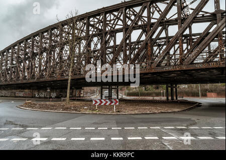 Rusty railroad bridge passing over a street - Stock Photo