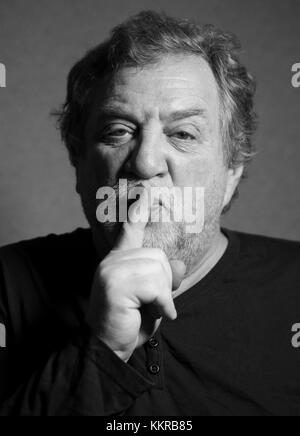 black and white portrait of middle aged caucasian man who put his index finger to his lips, calling for silence - Stock Photo